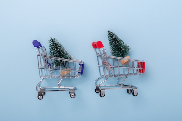 Mini shopping carts and small decorative fir tree on blue background Premium Photo