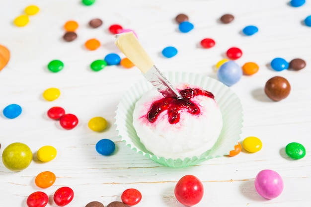 Mini white muffin between little colourful candies Free Photo