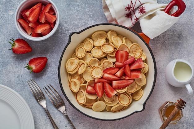 灰色の背景に朝食用フライパンにイチゴとミニ白いパンケーキシリアル Premium写真