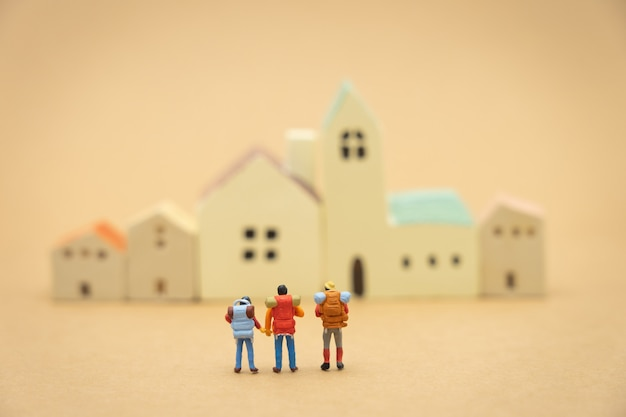 Miniature 3 people stand on house and hotel models to choose a place to live in. Premium Photo