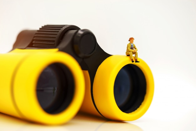 Miniature business people sitting on top of binoculars for finding people to work Premium Photo