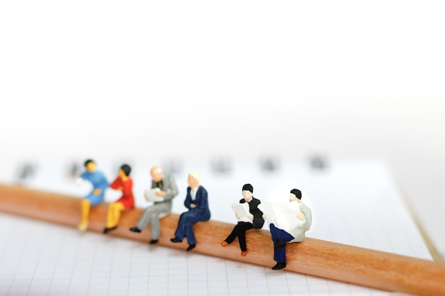 Miniature business team sitting on pencil and book. Premium Photo