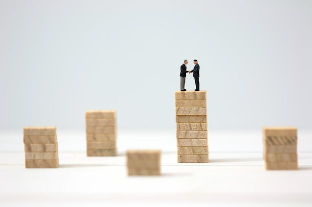 Miniature businessman cooperate on highest wooden stacks. Premium Photo