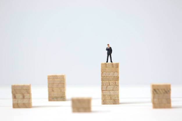 Miniature businessman making the decision on highest wooden stacks. Premium Photo