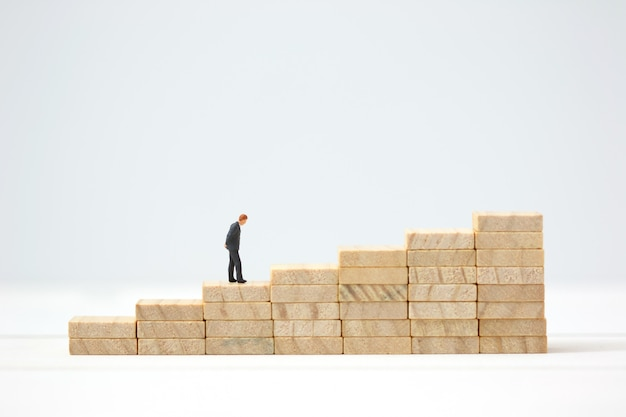 Miniature businessman making the decision on wooden graph. Premium Photo