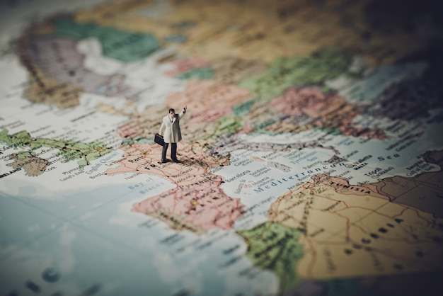 Miniature businessman on map of europe Free Photo