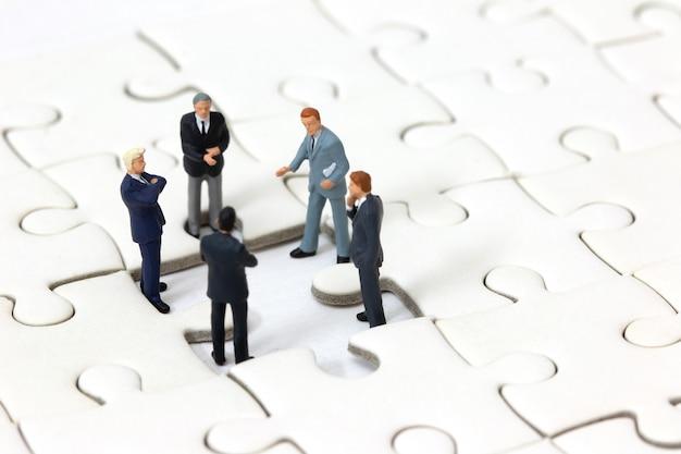 Miniature businessman meeting about lost jigsaw one piece. Premium Photo