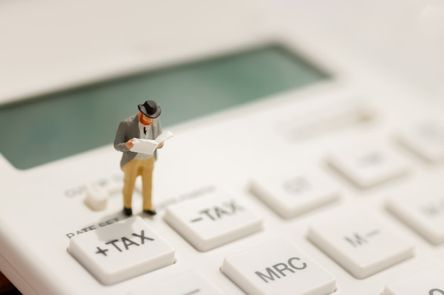 Miniature businessman stand reading on tax button of calculator. Premium Photo