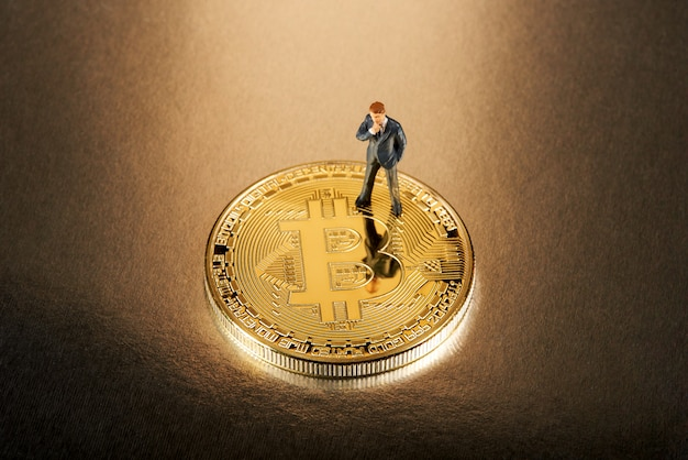 Miniature businessman standing on a bitcoin Premium Photo