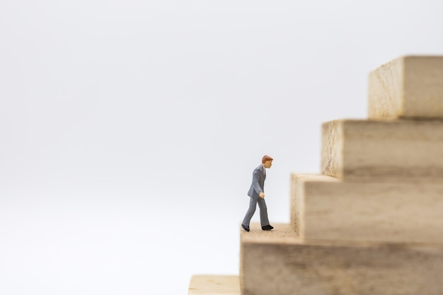 Miniature of businessman walking to top of stack of wooden block toy Premium Photo