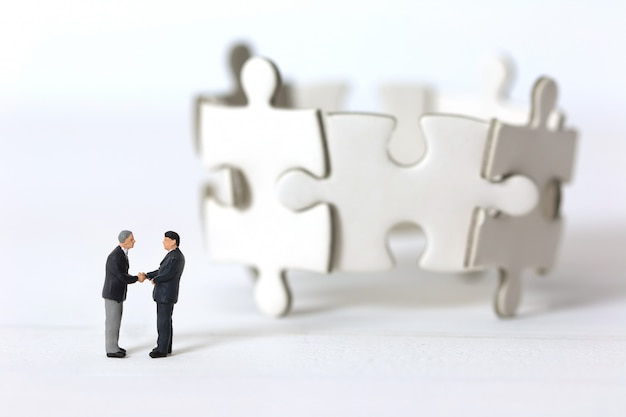 Miniature businessmen shaking hands on blurred group of jigsaw puzzle background. Premium Photo