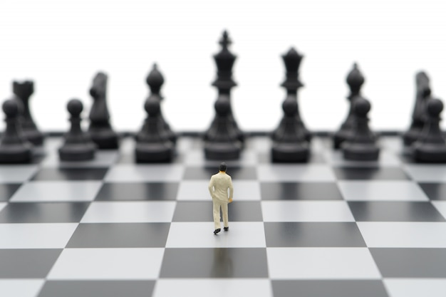 Miniature businessmen standing on a chessboard with a chess piece on the back. Premium Photo