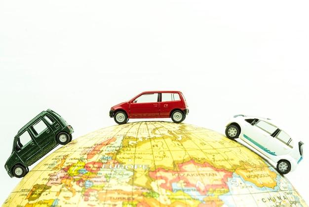 Miniature car around the globe close up. Premium Photo