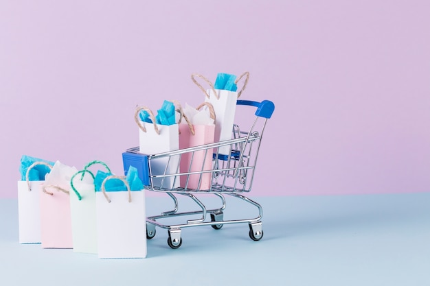 Miniature cart filled with paper shopping bags on blue surface Free Photo