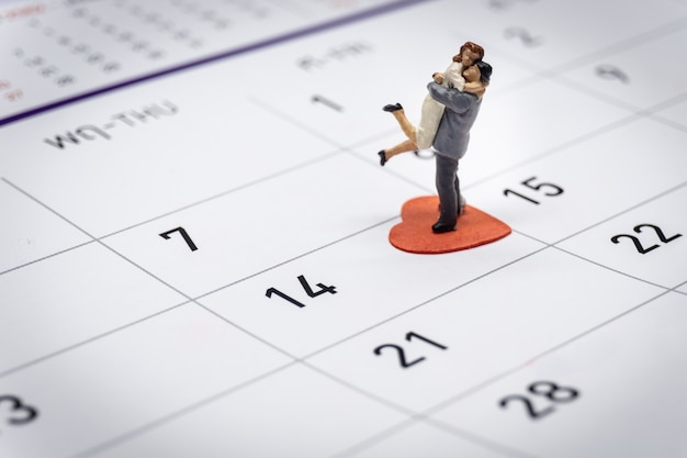 Miniature couple standing on calendar Premium Photo