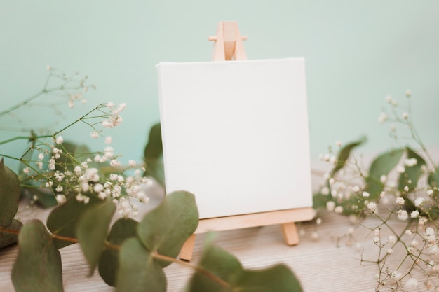 Miniature easel with blank canvas decorated with leaves and baby's-breath flowers against pastel background Free Photo