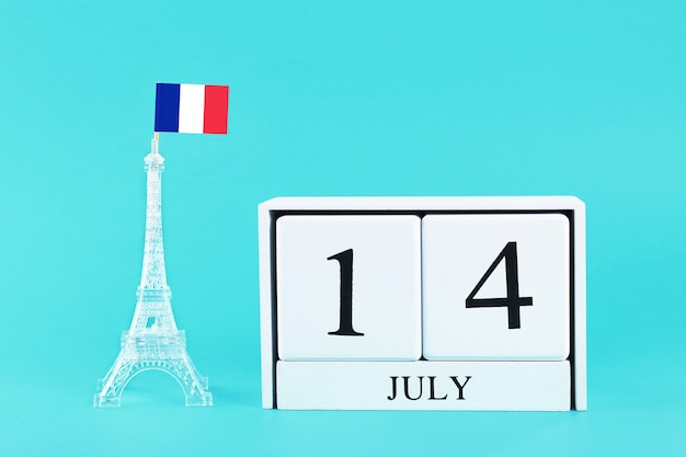 Miniature eiffel tower with a french flag and calendar. the concept is july 14, day of the Premium Photo