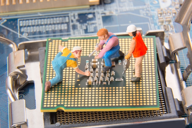 Miniature engineers or technician workers repairing cpu on the motherboard Premium Photo