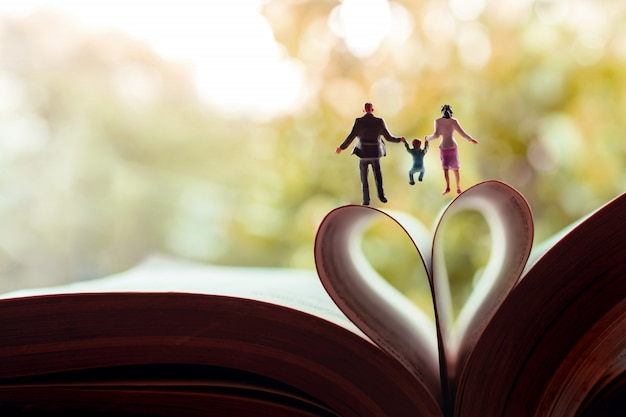 Miniature of father, mother and son holding hands and walking toward the book over a page roll like heart shape Premium Photo