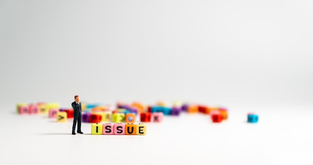 Miniature figure businessman standing beside of issue alphabet and thinking Premium Photo