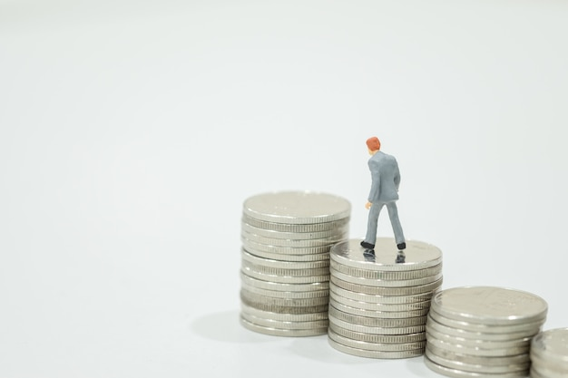 Miniature figures businessman walking to top of stack of coins Premium Photo