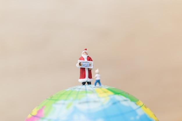 Miniature figures of santa claus holding gift Premium Photo