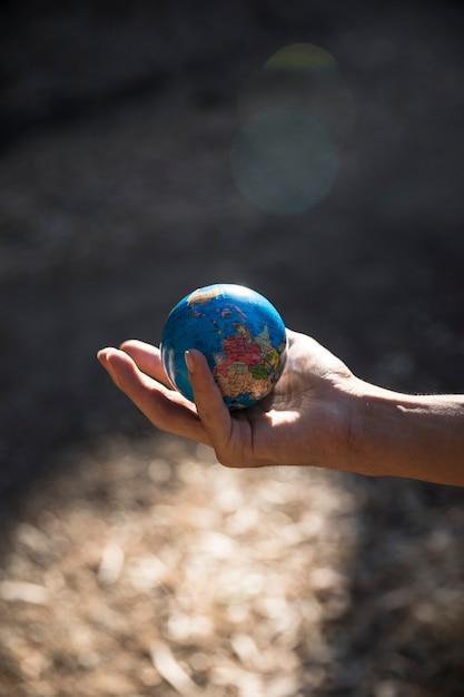 Miniature globe in hand in nature Free Photo