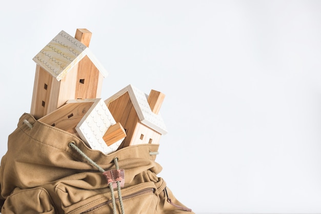 Miniature house model in the brown color backpack, property investment concept, copyspace, Premium Photo
