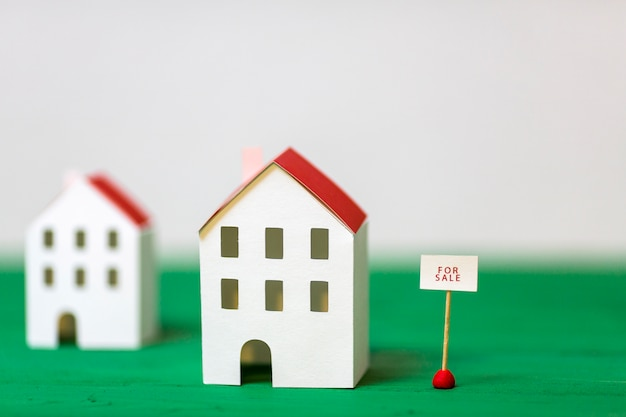 Miniature house model near the sale tag on green textured desk against white backdrop Free Photo