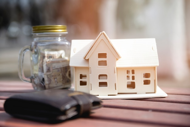 Miniature house with savings jar and wallet Free Photo