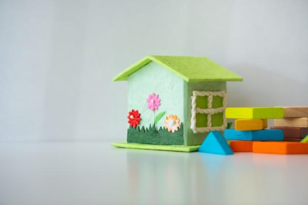 Miniature house with tangram puzzle on white background Premium Photo