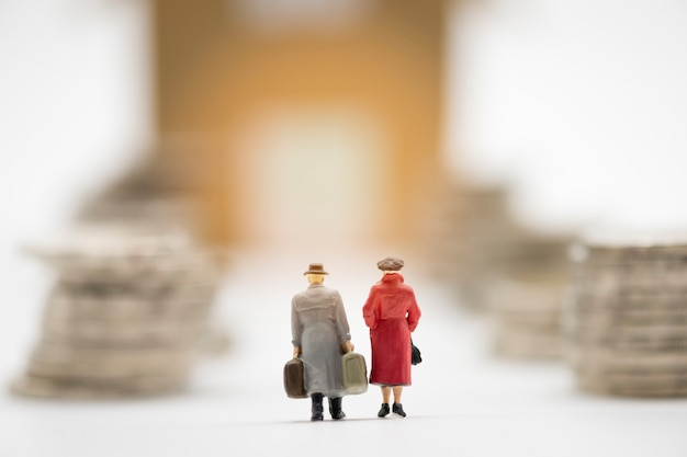 Behind miniature man and woman model hand carry suitcase and walk through coins stacking for move to new house. Premium Photo