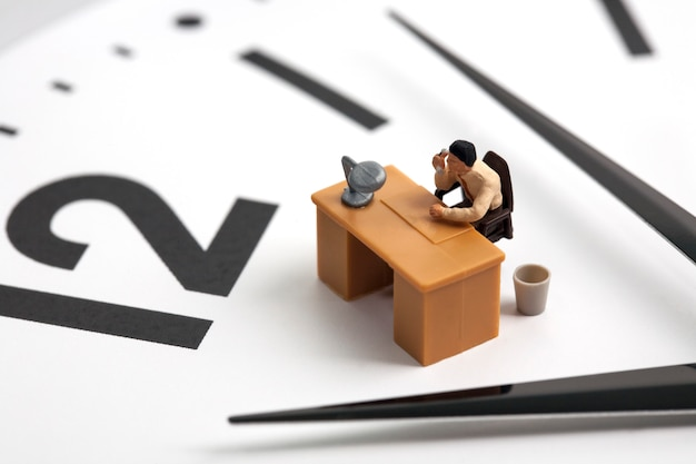 Miniature man working on clock background Premium Photo
