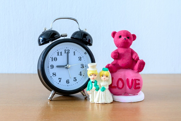 Miniature married couple and teddy bear and clock on wooden. concept for wedding & valentine day. Premium Photo
