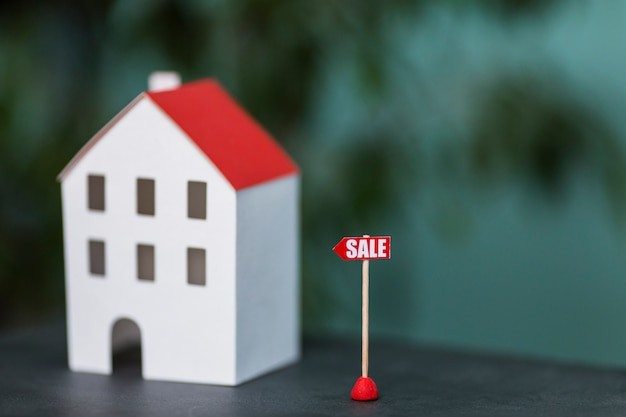 Miniature model of house real estate for sale against blurred backdrop Free Photo