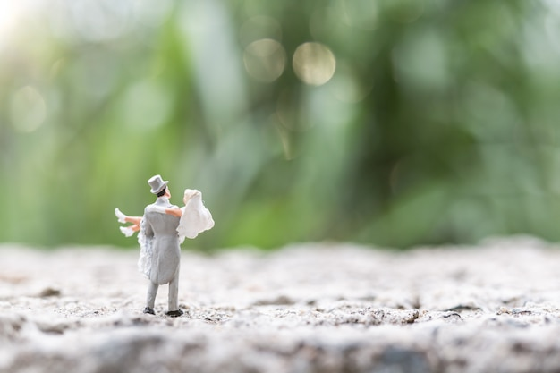 Miniature people:  bride and groom couple standing outdoor Premium Photo