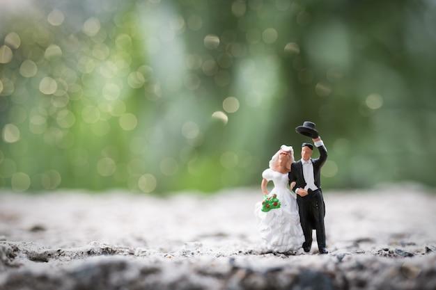 Miniature people:  bride and groom couple standing outdoor Premium Photo