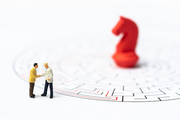 Miniature people, businessman and chess pieces in the labyrinth or maze figuring out the way out. Premium Photo