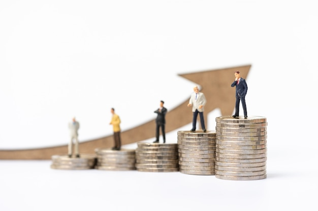 Miniature people, businessman on coins stack with arrow wooden icon. Premium Photo