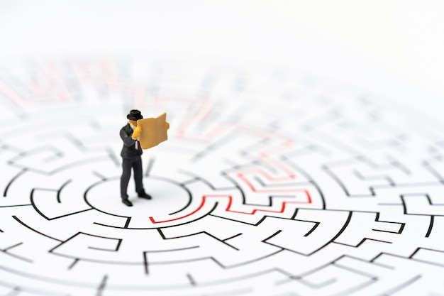 Miniature people, businessman in the labyrinth or maze figuring out the way out. Premium Photo