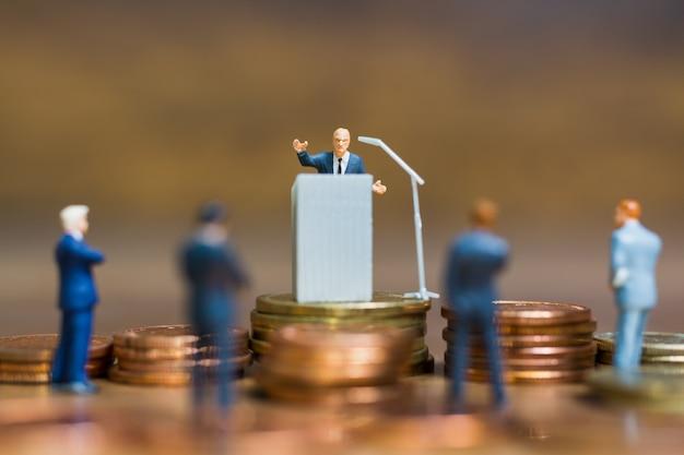 Miniature people: businessman speaking on the podium Premium Photo