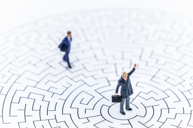 Miniature people businessman standing on center of maze using Premium Photo