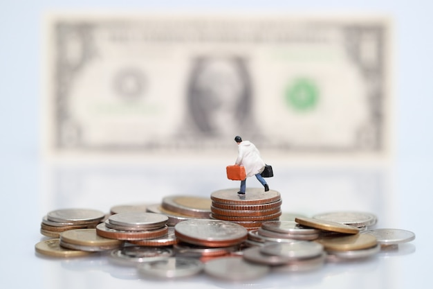 Miniature people: businessman standing on stacking coins Premium Photo