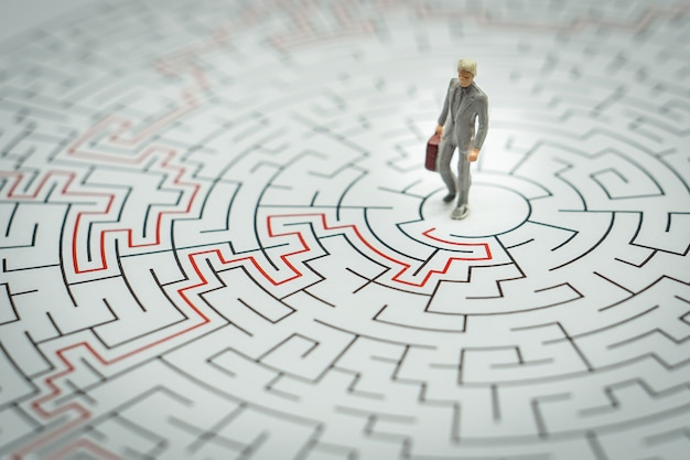 Miniature people businessman walking into a maze. Premium Photo