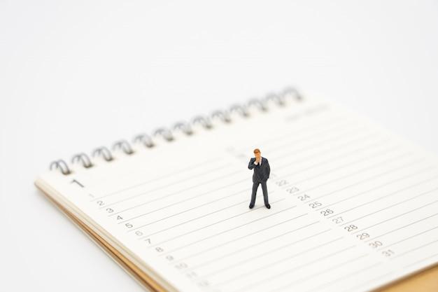 Miniature people businessmen analyze standing on a book rankings (list). Premium Photo
