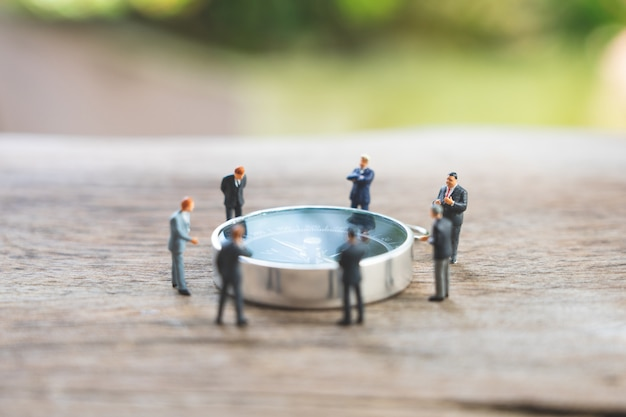 Miniature people businessmen analyze standing on compass as background strategy Premium Photo