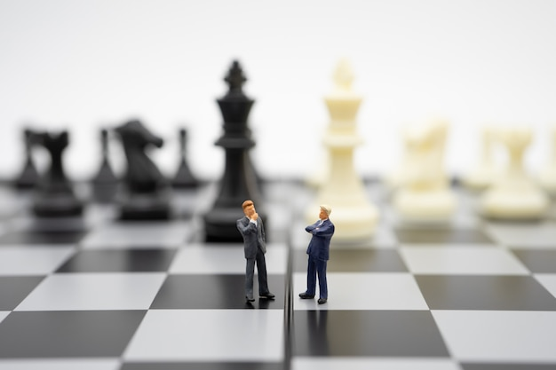 Miniature people businessmen standing on a chessboard with a chess piece on Premium Photo