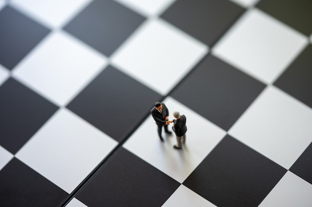 Miniature people businessmen standing on a chessboard with a chess piece Premium Photo