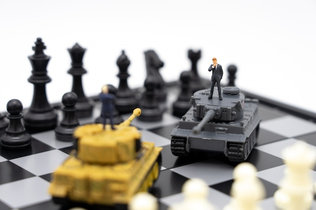 Miniature people businessmen standing on a chessboard with a tank model Premium Photo