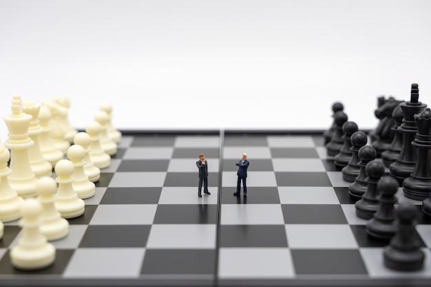 Миниатюрные люди-бизнесмены стоят на шахматной доске с шахматной фигурой Premium Фотографии